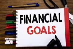 Handwritten text showing Financial Goals. Business concept for Income Money Plan Written on notebook, wooden background with offic. Handwritten text showing Stock Photography