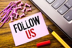 Handwritten text showing Follow Us. Business concept for Social Media Marketing written on pink sticky note paper on the wooden ba Stock Image