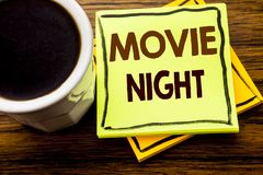 Handwritten text showing Movie Night. Business concept for Wathing Movies written on sticky note paper on the wooden wood backgro. Handwritten text showing Movie stock photos