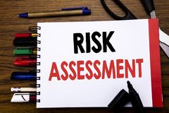 Handwritten text showing Risk Assessment. Business concept for Safety Danger Analyze Written on notebook, wooden background with o. Handwritten text showing Risk Royalty Free Stock Photography