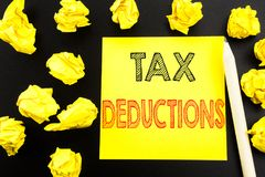 Handwritten text showing Tax Deductions. Business concept writing for Finance Incoming Tax Money Deduction written on sticky note. Paper on black background Stock Photo