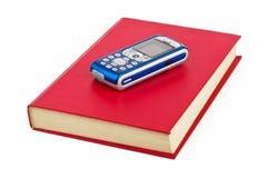 Handy auf Buch Lizenzfreie Stockbilder