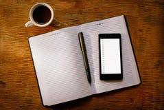 Handy auf einem offenen Tagebuch oder einer Zeitschrift Stockbilder