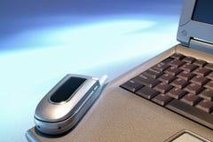 Handy auf Geschäfts-Laptop über geöffnetem blauem Platz Stockfotos