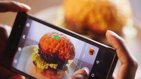 Handy, der einen Burger fotografiert Hamburger auf Cafétabelle lizenzfreies stockfoto