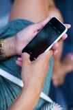 Handy in der Hand einer Frau in der Stadt nachts Stockfotografie