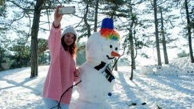 Handy in der Hand einer jungen Frau, die Spaß selfie Foto im Winterwald hintergrundbeleuchtetes, nettes Mädchen macht Foto mit a  stock video