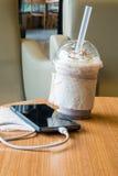 Handy, der im Café mit einer Plastikschale gefrorenem Schokolade frappe auflädt stockfoto