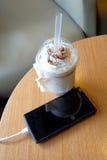 Handy, der im Café mit einer Plastikschale gefrorenem Schokolade frappe auflädt stockfotografie