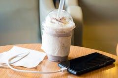 Handy, der im Café mit einer Plastikschale gefrorenem Schokolade frappe auflädt stockfotos