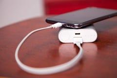 Handy, der mit Energie-Bank auflädt Stockbild