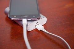 Handy, der mit Energie-Bank auflädt Lizenzfreies Stockbild