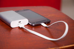 Handy, der mit Energie-Bank auflädt Stockfotografie