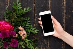Handy in der weiblichen Hand und ein Blumenstrauß von Blumen auf einem schwarzen hölzernen Hintergrund stockfotografie