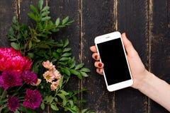 Handy in der weiblichen Hand und ein Blumenstrauß von Blumen auf einem schwarzen hölzernen Hintergrund lizenzfreie stockfotos