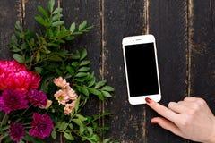 Handy in der weiblichen Hand und ein Blumenstrauß von Blumen auf einem schwarzen hölzernen Hintergrund stockfotos