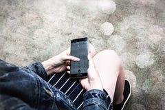 Handy in Frau ` s Hand auf unscharfem Hintergrund, Mädchen untersucht Smartphone auf Lichter bokeh Weichzeichnung, Weinlese Stockfotos