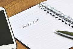 Handy, geöffnetes Notizbuch und Stift mit, zum der Listen-Anmerkung zu tun Stockfotos
