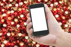 Handy an Hand mit unscharfem Hintergrund des Weihnachtsbaums Lizenzfreies Stockbild