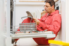 Handy Man. Figuring out a way to fix the dishwasher in the kitchen Royalty Free Stock Image
