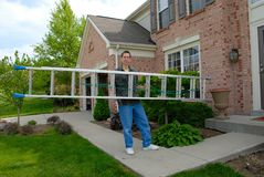 Handy Man Ladder. A man carrying an aluminum ladder toward the front door of a brick house in the springtime Stock Image