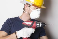Handy man with protective clothes drilling hole in wall. Handy man with protective clothes holding drilling machine Stock Photography