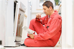Handy Man. Reading the instruction manual in front of the dishwasher in the kitchen. Copy space Stock Photo