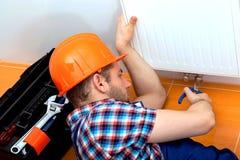 Handy man repairing heater. Handy man in a hard hat repairing heater Stock Images