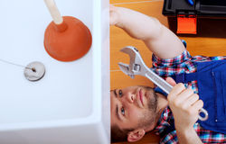 Handy man repairing sink in bathroom. Young handy man repairing sink in a bathroom Stock Images