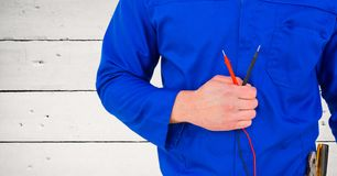 Handy man standing with cables against wooden background Royalty Free Stock Image