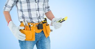Handy man standing with tools against blue background Royalty Free Stock Photography