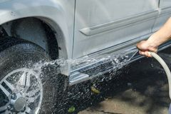 Handy man washing car by himself.  Royalty Free Stock Images