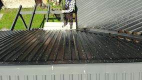 Handy man washing roof with high pressure stock footage