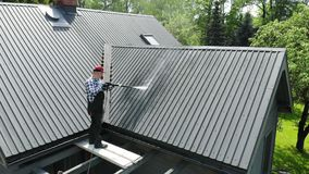 Handy man washing roof with high pressure stock video footage
