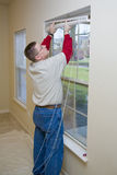 Handy Man Working. Repair man replacing window blinds in apartment, Making ready for new tenant Royalty Free Stock Photo