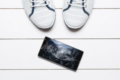 Handy mit defektem Schirm auf Bretterboden stockbild