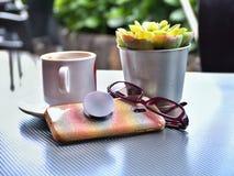 Handy mit der Rückseite und schillernde Hülle auf Tabelle beim Trinken des Kaffees stockfoto
