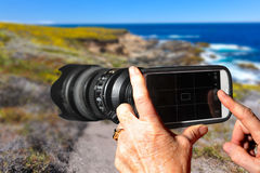 Handy mit einem Teleobjektiv befestigt Stockbilder