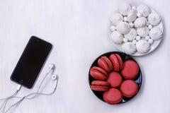 Handy mit Kopfhörern, Makronen und Meringen auf weißer Tabelle Stockbild