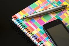 Handy mit Notizbuch und Ballpoint Lizenzfreie Stockfotos