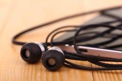 Handy mit Paaren des Kopfhörers Stockfotografie