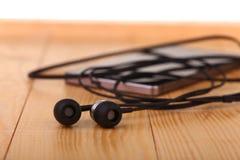 Handy mit Paaren des Kopfhörers Lizenzfreie Stockbilder