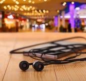 Handy mit Paaren des Kopfhörers Lizenzfreie Stockfotos