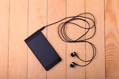 Handy mit Paaren des Kopfhörers Lizenzfreies Stockbild