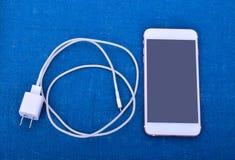 Handy mit verbundenem Stecker des Ladegeräts stockbild