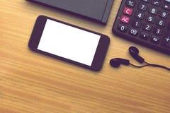 Handy mit weißem Schirm, Kopfhörern und Taschenrechner Lizenzfreie Stockfotografie
