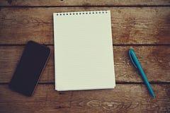 Handy, Notizbuch und Stift auf altem Holztisch Stockbild