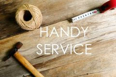 Handy service written on wooden background with rope,hammer and measuring tape royalty free stock image