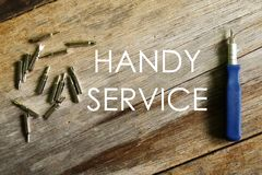 Handy service written on wooden background with screwdriver royalty free stock photography