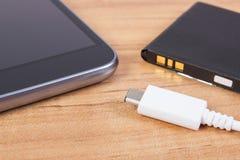 Handy, Stecker des Ladegeräts und Telefonbatterie, Smartphoneaufladung Lizenzfreies Stockbild
